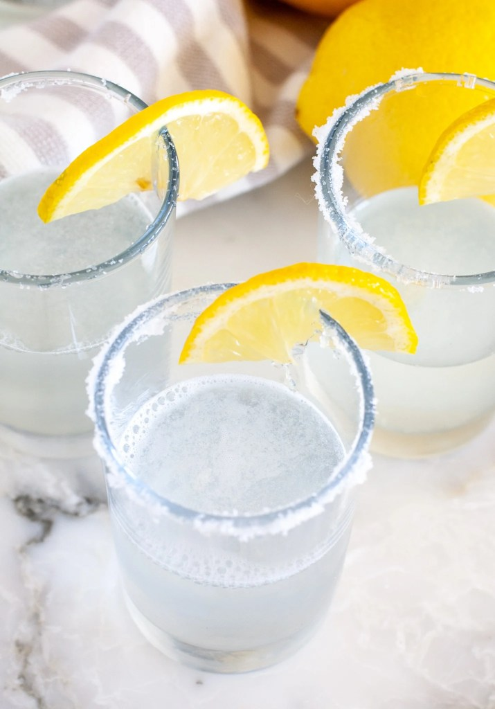 Shot glass with vodka and lemon wedge
