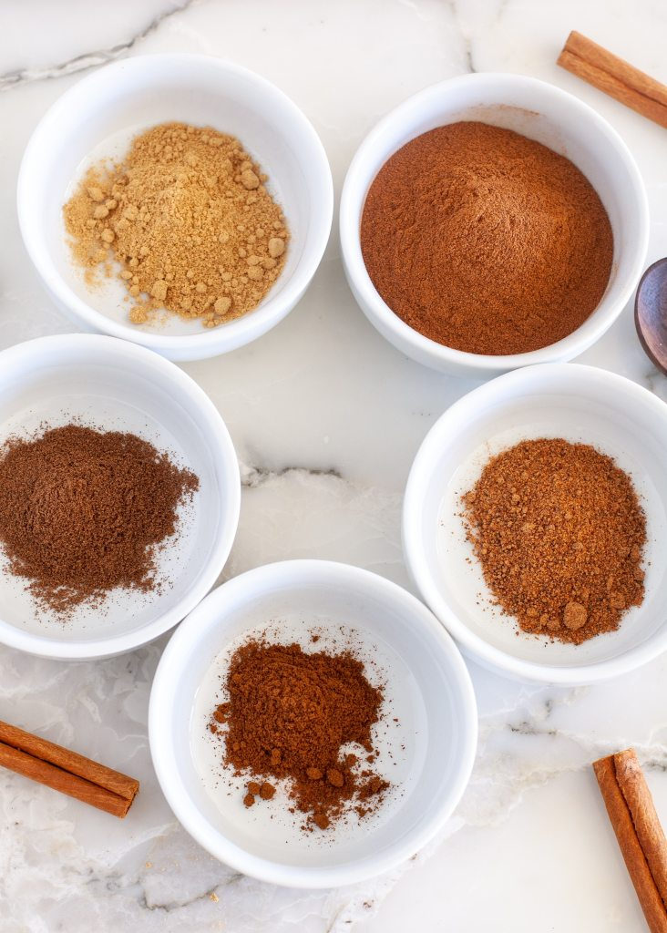 spices in bowls with cinnamon sticks