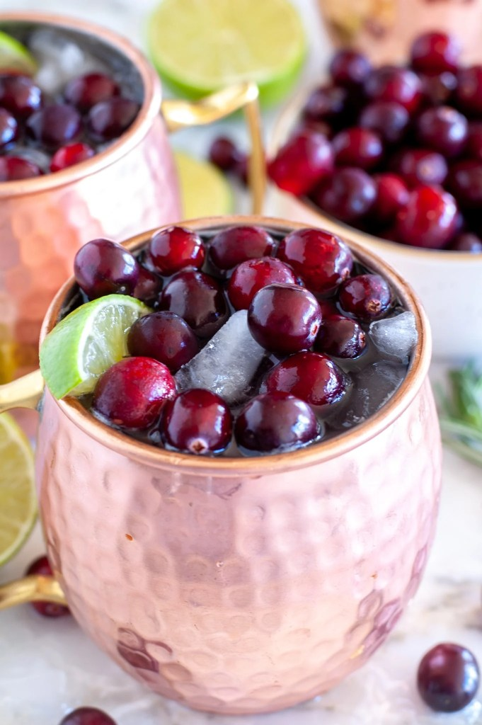 Copper cup with ginger beer, cranberry juice and lime wedge.