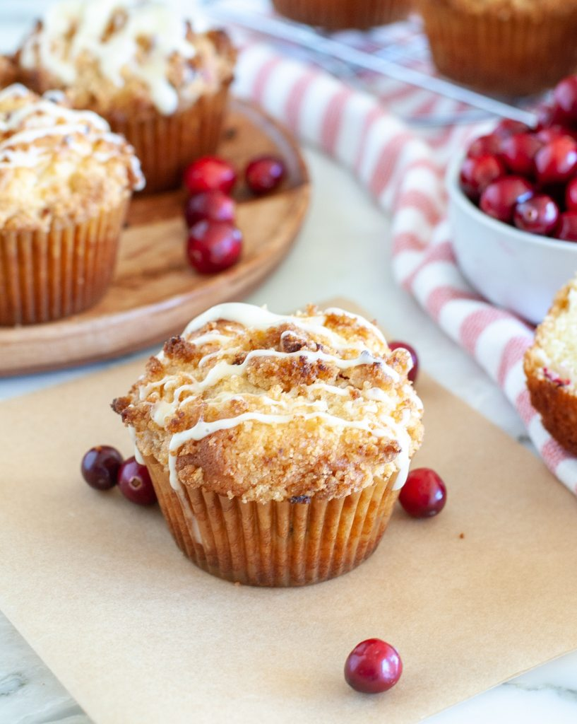 Muffin on paper with cranberries.