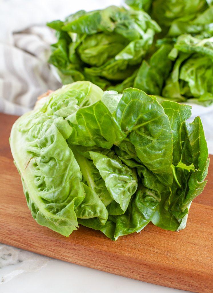 Head of lettuce on cutting board.