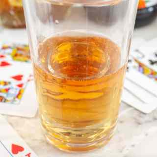 Glass filled with energy drink and playing cards beside the glass.