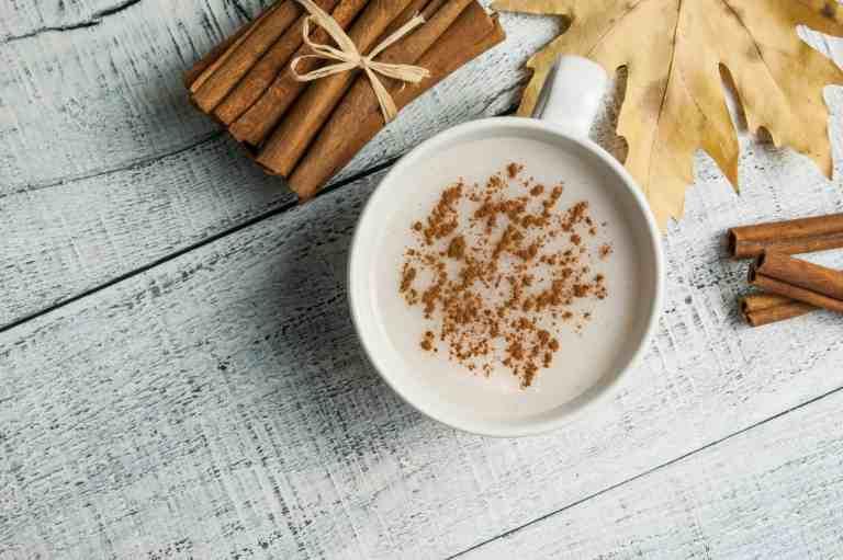 Zimtstangen neben Tasse Milch mit Zimtpulver