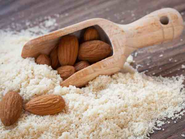almond flour, almonds in a dark wood background