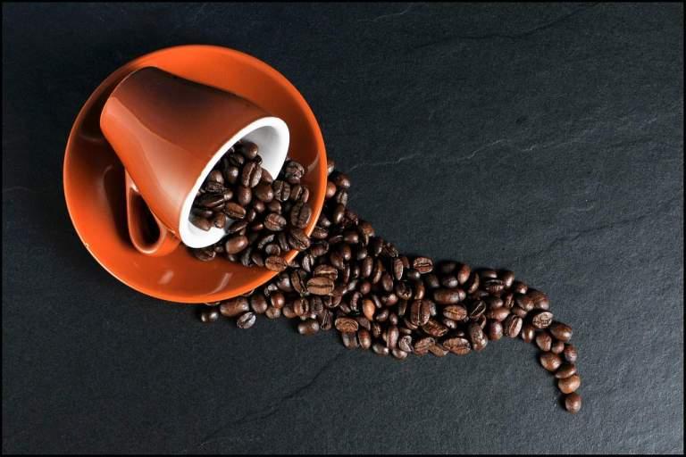 Rote Kaffeetasse mit Kaffeebohnen auf Steinplatte