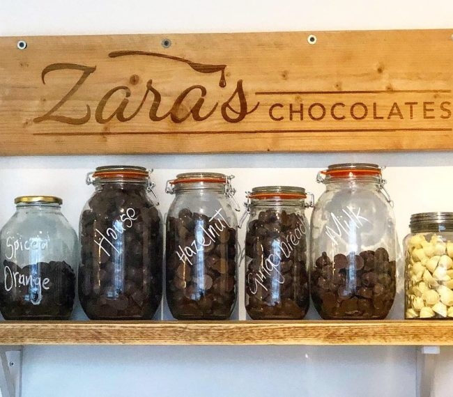 Zara's Chocolates Shelf of Hot Chocolate Jars and Shop Sign