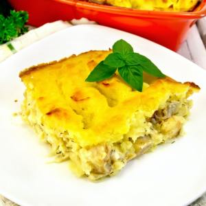 Gratin potato with fish in plate on light board