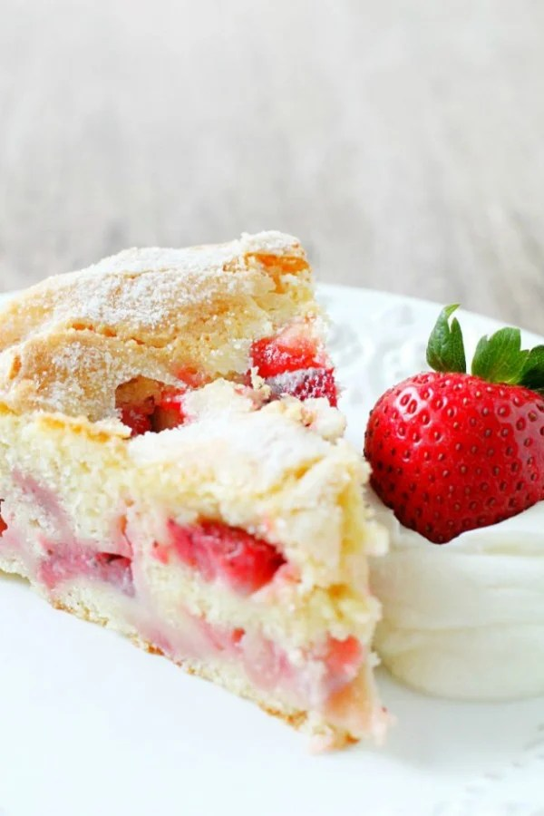 slice of french strawberry cake on plate with whole strawberry and whipped cream
