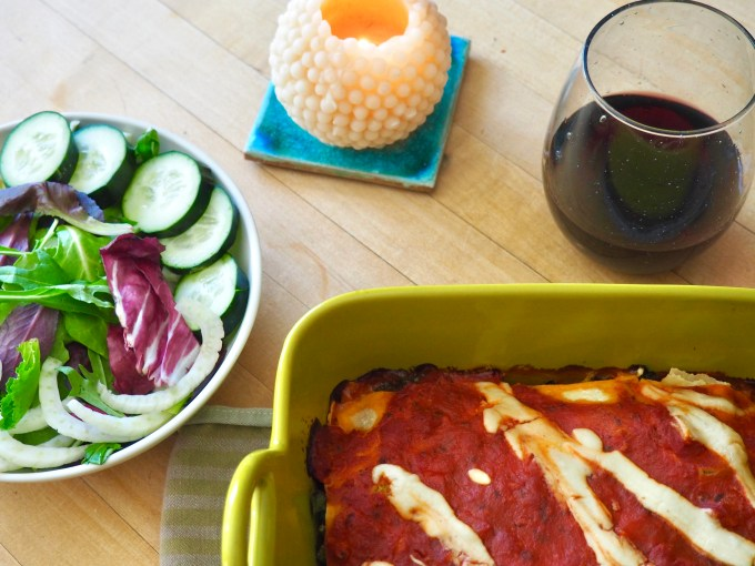 table with dish of lasagna side salad red wine and a candle