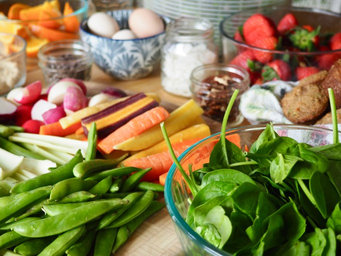 Easy Healthy Meal Prep table full of chopped fruits, veggies, greens, nuts, muffins and eggs