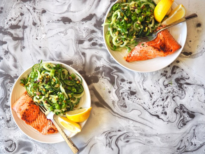 cucumber noodle salad with easy lemon seared wild salmon and lemon wedges on a marbled table