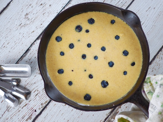 batter and blueberries in a cast iron skillet for Coconut Flour Blueberry Skillet Bread