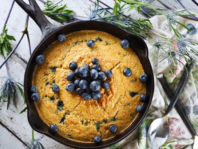 overhead view of Coconut Flour Blueberry Skillet Bread on wood table with flowers and spoon