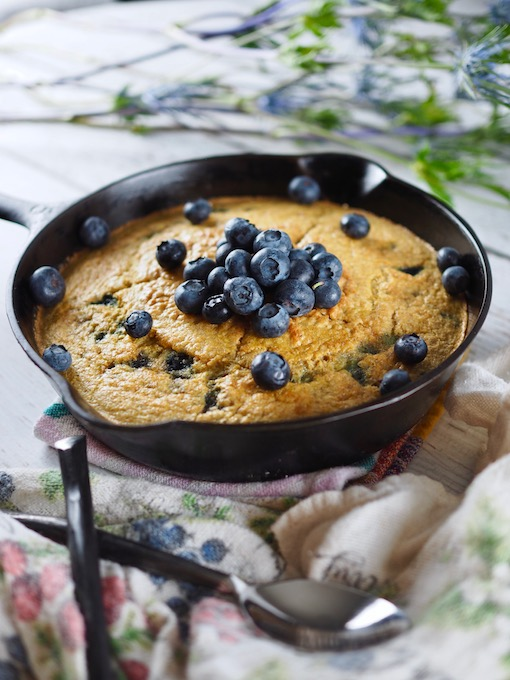 side view of Coconut Blueberry Skillet Bread with wrought iron spoons and flours