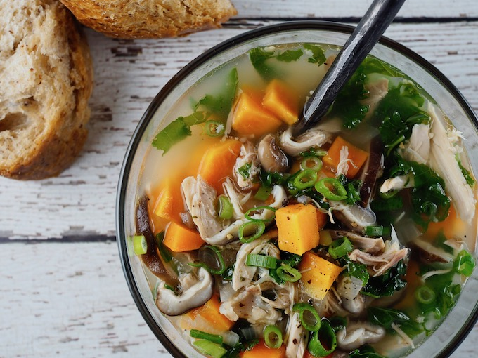 glass bowl of Paleo Sweet Potato Chicken Soup with bread on white wooden table