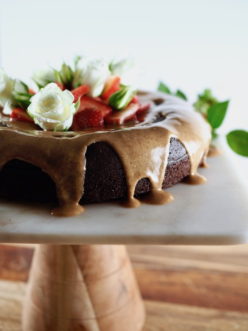 side view of Ultimate Paleo Flourless Chocolate Cake with Honey Almond Butter Glaze dripping down the sides, on marble cake platter with white roses and strawberries