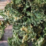 easy tahini garlic kale chips in a pile on a wooden table