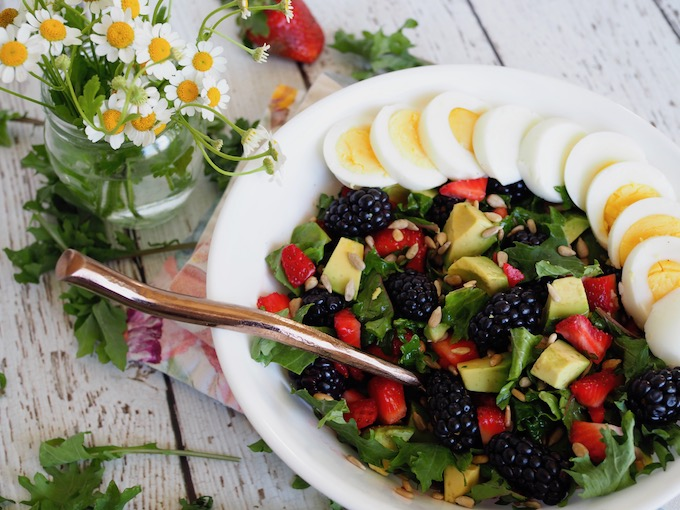 Baby Kale Berry Breakfast Salad on white table with kale scattered around
