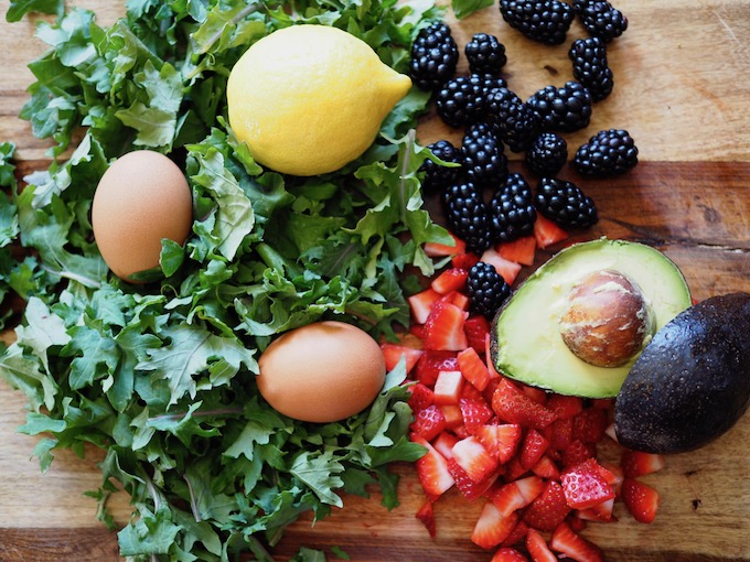 baby kale lemon eggs blackberries strawberries and avocado on wooden cutting board