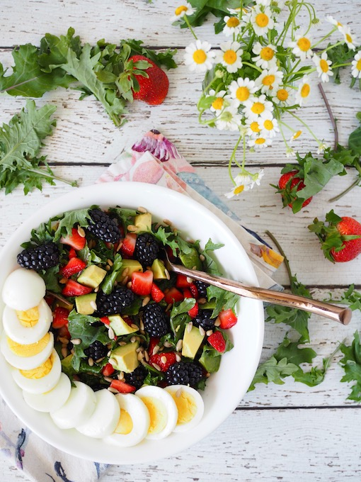 Baby Kale Berry Breakfast Salad with scattered berries and kale on white wood table