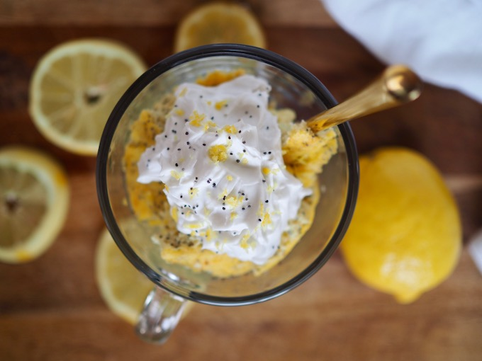 glass mug filled with lemon poppy seed coconut flour skillet bread, topped with coconut cream, lemon zest and poppy seeds, with lemons scattered around it
