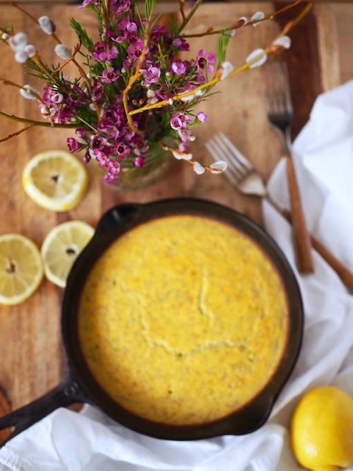 lemon poppy seed coconut flour skillet bread on wood table with forks, flowers, and lemons scattered around it