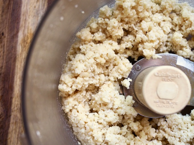 food processor filled with macadamia nuts and coconut blended into a shortbread crumble