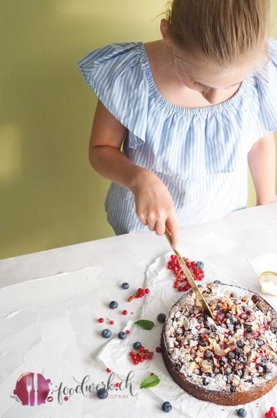 Der Beerenkuchen wird von Liv mit einem goldenen Messer angeschnitten.