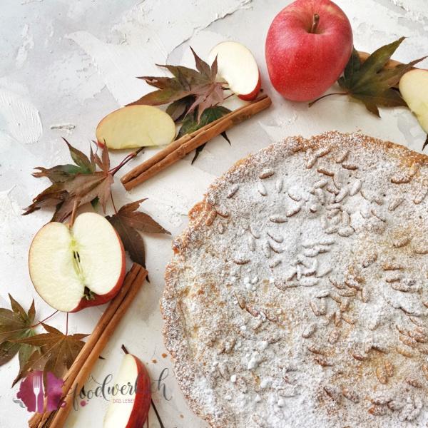 Klassische Torta della Nonna mit Apfel. Fotografiert mit rotem Herbstlaub und geschnittenen Äpfeln.
