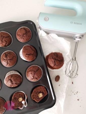 Schokoladenmuffins und Bosch Handrührgerät. Die Muffins sind mit Schokobons gefüllt.