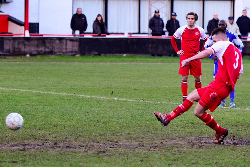 Jake White takes a penalty on a very muddy Larges Lane pitch at Bracknell Town. Photo: Neil Graham.