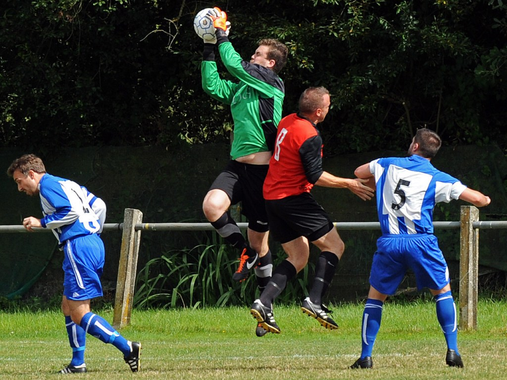 Sandhurst Town number eight Richard Hughes takes on Chalfont keeper Mark Sweeney in the first half. Photo: Mark Pugh.