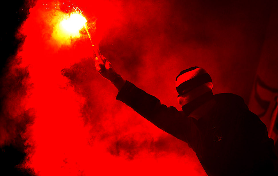 Football Politics: A supporters of Young Boys of Bern lights a flare during during a Champions League Group Play-off first leg football match against Tottenham Hotspur on August 17, 2010, at the Stade de Suisse, in Bern. TOPSHOTS/AFP PHOTO/FABRICE COFFRINI (Photo credit should read FABRICE COFFRINI/AFP/Getty Images)