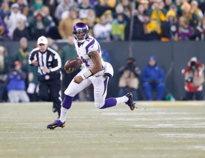 Referee Scott Green follows Vikings quarterback Joe Webb. (Minnesota Vikings photo)