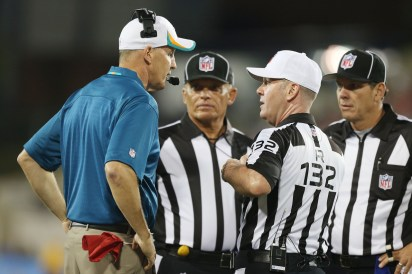 Joe Philbin speaks to referee John Parry (132) during the Hall of Fame game as side judge Tom Hill (left) and field judge Scott Edwards (right) look on.