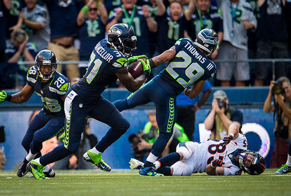Seattle Seahawks strong safety Kam Chancellor intercepts a pass during a regular season game against the Denver Broncos. Intended receiver Wes Welker falls to the ground after being hit by Earl Thomas III. (Seattle Seahawks photo)