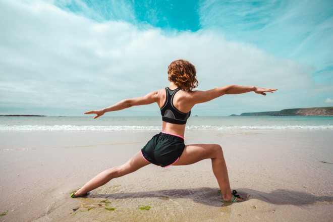 woman stretching in sand