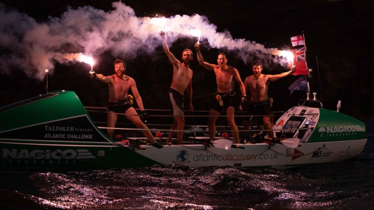Four men holding flares on a boat cheering