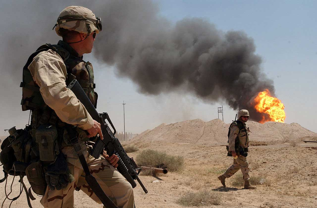 US soldiers near a burning oil well in the Rumaylah oil fields in southern Iraq, April 2, 2003. (Arlo K. Abrahamson/US Navy)