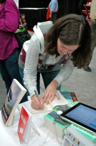 Shasta Kearns Moore autographs her essay in Brave on the Page. The publisher/author will be one of our booth volunteers this year.