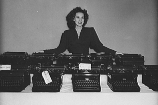 """Hollywood joined the typewriter campaign. The original caption on this 1942 photo of actress Maureen O'Hara: """"The stories they've told! Another load of RKO Radio typewriters is turned in to the government for war work. Somewhere in the lot is Maureen O'Hara's personal typewriter which she added to the pile before she would pose in the picture. The machines come from the script department where each one has played its role in recording countless memorable scenes for screenplays. Taking time off between the shooting of scenes at the RKO Studios in Hollywood, Miss O'Hara helped collect more than seventy typewriters for future use by the Army, Navy, and Marines."""" (Library of Congress photo)"""