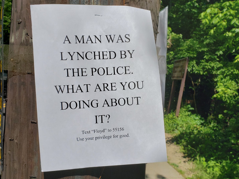"A sign by the Albemarle Street entrance to Soapstone Park: A MAN WAS LYNCHED BY THE POLICE.  WHAT ARE YOU DOING ABOUT IT? Text ""Floyd"" to 55156. Use your privilege for good."
