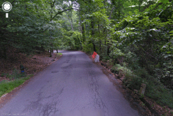 From a 2011 Google Streetview image, one of the block's blind curves, with makeshift crash barriers.