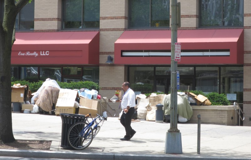 A passerby walks past the makeshift camp in front of the Fannie Mae building at 4250 Connecticut Avenue.