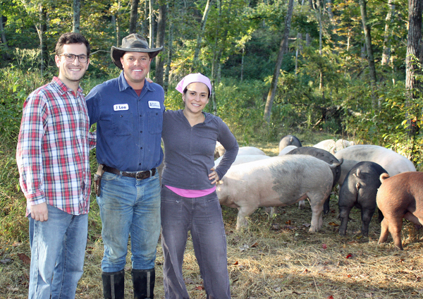 Left to right: Matt Carr, Polyface Farm's Daniel Salatin, Anne Alfano and some of the farm's residents. The pigs root around in the forest for acorns, grubs and other grub. (photo provided by Little Red Fox)