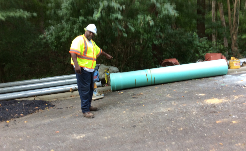 DC Water's John Crowder points to an 18-inch PVC pipe from which a piece was cut. (photo by David Jonas Bardin)