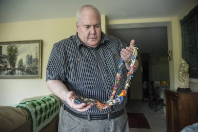 Larry Armstrong holds a necklace handmade from origami cranes at his home in Forest Park. Armstrong bought the necklace back in the '80s. (By ALEXA ROGALS/Staff Photographer)