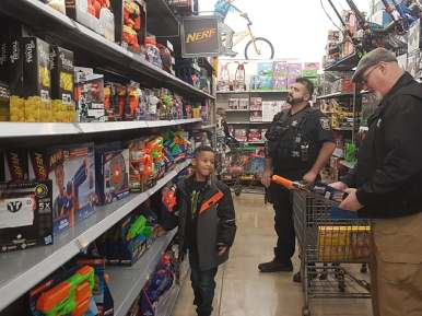 Theo Christo spends time examining Nerf guns with Forest Park's Officer Dan Miller and Detective Jarlath Heveran at Walmart on Dec. 14.