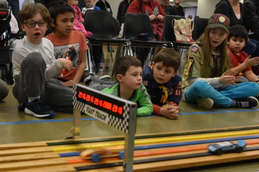 Scouts, including brothers Henry and Dylan Kernkamp, watch as the race cars come down the track. | Photo by Jill Wagner