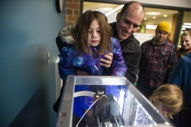 Solenn and Benn Joseph watch the 3-D printer. | Alex Rogals/Staff Photographer
